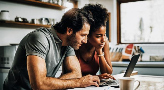 Man and woman sitting by a laptop