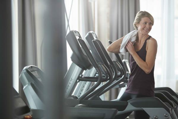 Female looking back on elliptical with towel on shoulder
