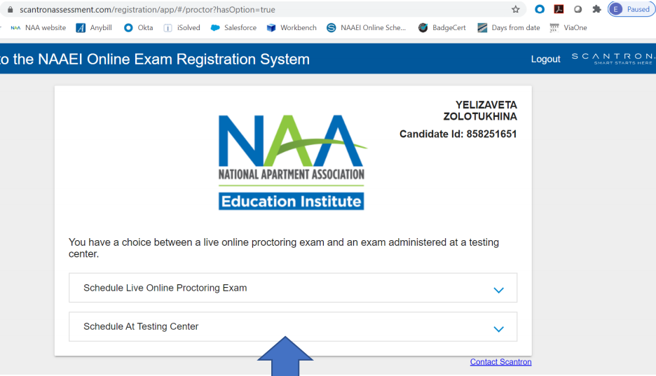 """A page for the user to choose which location they would like to take their test. A blue arrow points to the option, """"Schedule at Testing Center""""."""